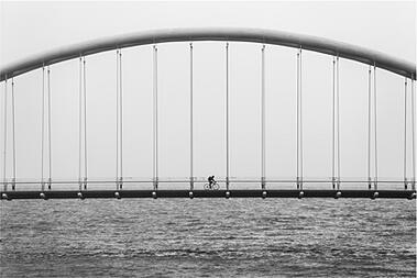 Man riding bike over bridge